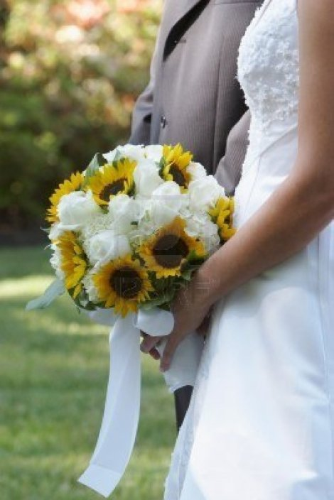 bride-holding-wedding-bouquet-flowers-against-dress