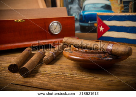 stock-photo-cuban-cigars-and-humidor-with-ashtray-on-rustic-wooden-table-with-cuban-painting-of-american-old-218521612
