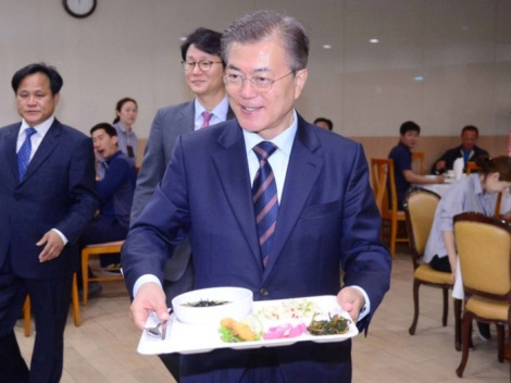 South Korean President Moon Jae-in carries a food tray as he has lunch with technical staff of the Presidential Blue House at an employee cafeteria of the Presidential Blue House in Seoul