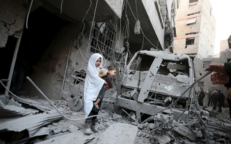 A girl carrying a baby inspects damage in a site hit by what activists said were airstrikes carried out by the Russian air force in the town of Douma, eastern Ghouta in Damascus, Syria